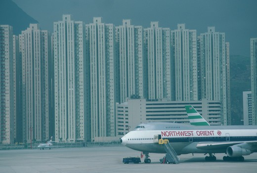 Stock Photo: 4286-80395 Grounded plane in Hong Kong Airport with subsidized housing in background