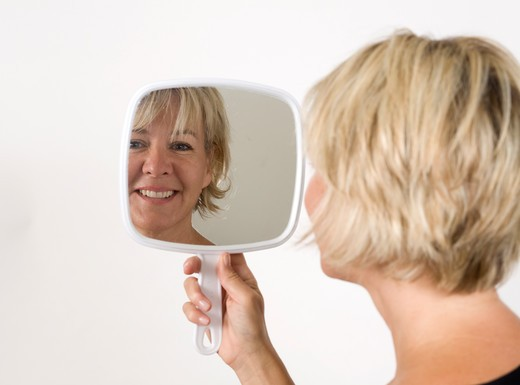 Stock Photo: 4286-81424 Mature woman holding hand mirror, smiling