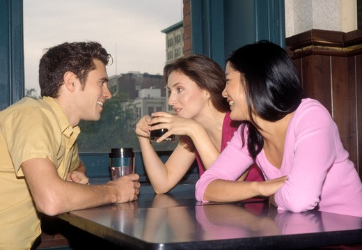 Stock Photo: 4286-81955 Friends sitting in coffee shop,side view
