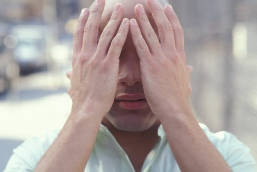 Young man covering face with hands : Stock Photo