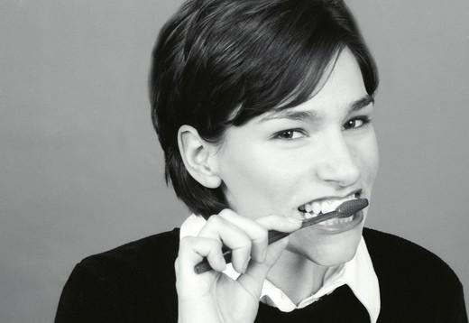 Young woman brushing teeth, portrait : Stock Photo