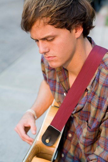 Young man playing guitar, smiling, portrait : Stock Photo