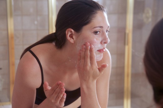 Stock Photo: 4286-84229 Woman looking into the mirror, washing her face