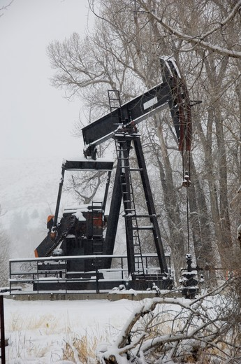 Oil and gas pumper in Wyoming winter. : Stock Photo