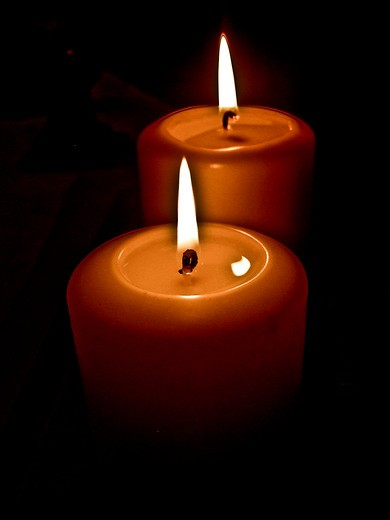 Stock Photo: 4286-85446 Two candles burning in the dark.