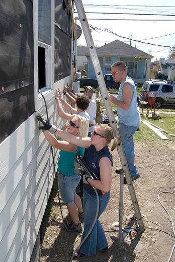 Group of young adults working and remodeling exterior of a house : Stock Photo