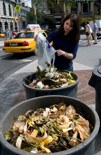 Stock Photo: 4286-85650 Union Square, NYC, 2009 - Young woman emptying a bag of food waste into compost heaps at an outdoor farmer's market.  Model Released - ?Marty Heitner