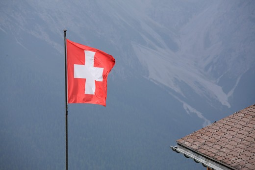 Swiss national flag with the Alps background, Switzerland : Stock Photo