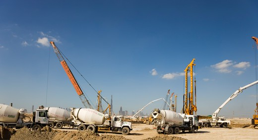 Stock Photo: 4286-89482 Dubai.  New construction site with piling rigs, concrete pump and ready mixed concrete trucks, against part of the  Dubai skyline with Burj Dubai.