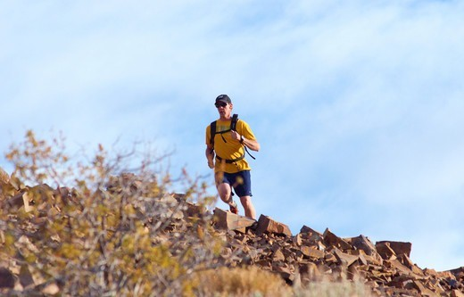 Stock Photo: 4286-90021 Athletic man running along a high mountain ridge in the High Sierras of California