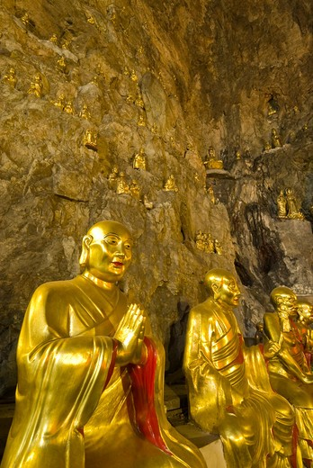 Golden Buddha statues line stone walls of temple cave, Yangdang Mountains, Wenzhou, Zheijiang Province, China : Stock Photo
