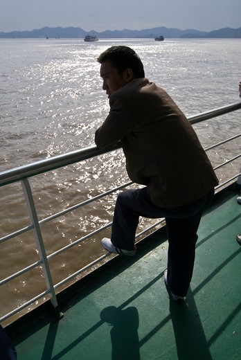 Man on ferry boat wathces the sea, Zhoushan, Zhejiang Province, China : Stock Photo