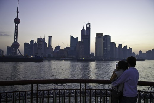 Stock Photo: 4286-90643 Young couple take photo with cellular phone and cuddle before dawn along skyline, The Bund, Shanghai, China