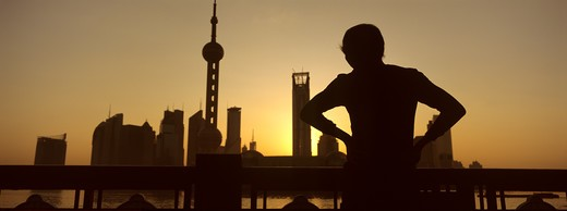 Stock Photo: 4286-90676 Sunrises over skyline as elderly man exercises tai chi, The Bund, Shanghai, China