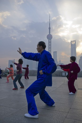 Stock Photo: 4286-90708 Costumed tai chi practitioners at dawn skyline, The Bund, Shanghai, China