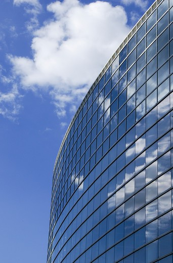 White clouds and a blue sky reflecting in the mirrored windows of a modern building. : Stock Photo