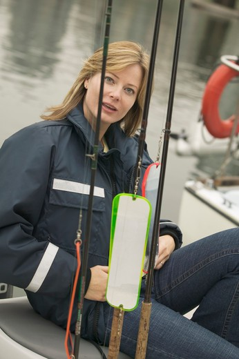 Woman wearing foul weather gear preparing to go fishing  MR-0423 PR-0424 : Stock Photo