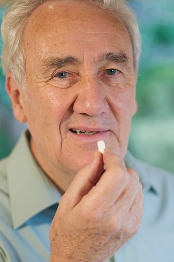 Stock Photo: 4286R-10655 Senior Taking Vitamin/Medication.