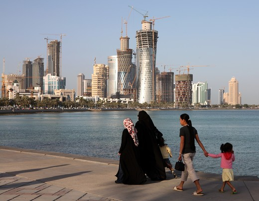 Covered Qatari women with their children and housemaid strolling on the Corniche in Doha, Spring 2008, with the New District construction work taking place across the Doha Bay. : Stock Photo