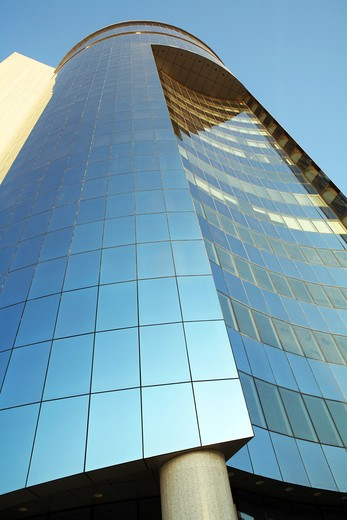 Stock Photo: 4286R-1187 An ultramodern, mirror-clad corporate tower rises into the blue sky
