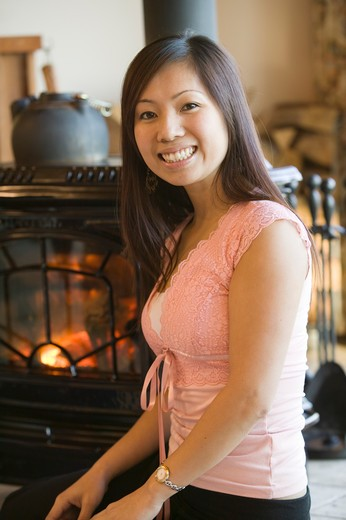 Asian Woman Sitting By a Wood Stove, MR-0562 PR-0505 : Stock Photo