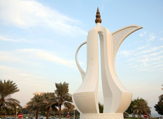 Stock Photo: 4286R-1212 The 'Dallah' coffee-pot monument on the Corniche in Doha, Qatar. The Doha Sheraton Hotel is visible behind palms bottom left A dallah is a symbol of welcome and hospitality in Arabia.