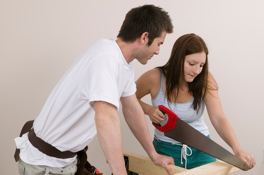 Stock Photo: 4286R-12253 Couple Sawing a Board
