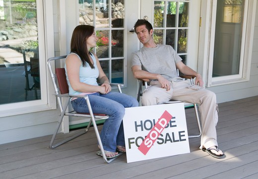 Stock Photo: 4286R-12312 Couple Sitting With a House For Sale Sold Sign