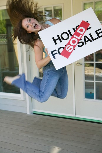 Woman Jumping For Joy With a House For Sale Sold Sign : Stock Photo