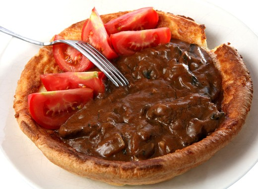 A big yorkshire pudding filled with stewed beef and mushrooms in gravy, topped off with wedges of tomato. : Stock Photo