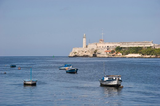 Small fishing boats dot the harbour entrance in front of the old lighthouse and citadel at the end of the Malecon, Old Havana : Stock Photo