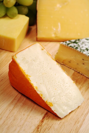 Stock Photo: 4286R-1325 Port Salut cheese on a board with a variety of other gourmet cheeses