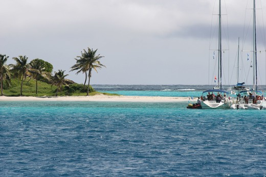 Pleasure boats anchored off deserted island in the Tobago Cays - Saint Vincent : Stock Photo