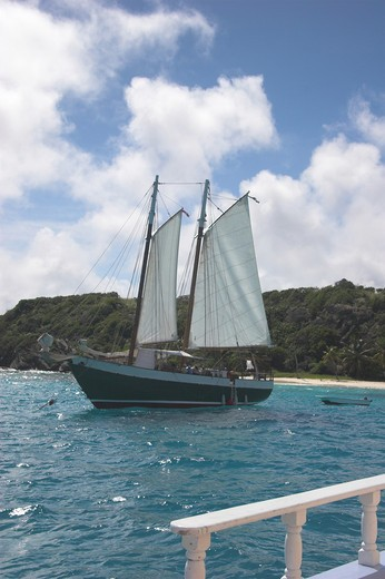 Two masted schooner pulls alongside with small island in the background - Tobago Cays : Stock Photo