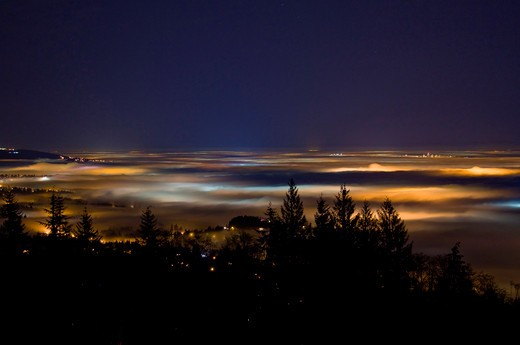 Up above Vancouver and the Fraser Valley shrouded in fog - Lights of the city cast colorful glows at night : Stock Photo