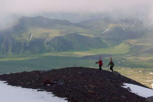 Two skiers climbing Mount Vsevidov in the Aleutian islands above green tundra. : Stock Photo