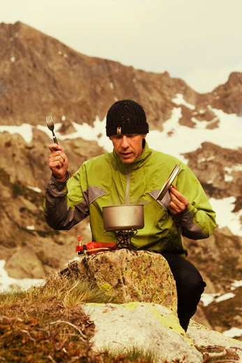 A proud man cooking while camping in the Southern Alps of France : Stock Photo