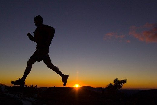 A man trail running at sunset in the mountains above Lake Tahoe California : Stock Photo