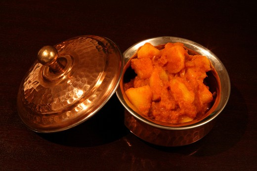 Stock Photo: 4286R-1525 An authentic Indian copper-clad serving bowl containing Punjabi potato curry, a north-Indian favourite, on a dark wood table.