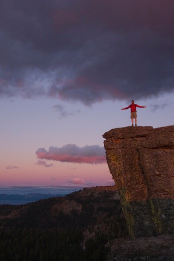 Stock Photo: 4286R-15376 A man standing on the edge of a cliff at sunset above Lake Tahoe in California