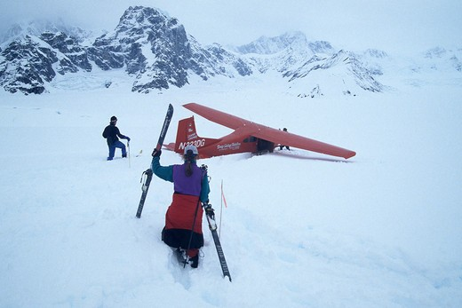 Three people and a red bush plane with skis stuck in deep snow in the Ruth Gorge in Denali National park in Alaska : Stock Photo
