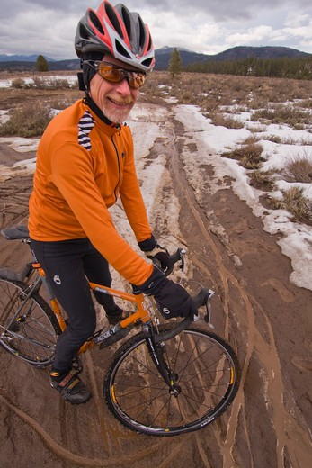 Stock Photo: 4286R-16195 a man with a cyclocross bicycle in mud on an overcast winter day