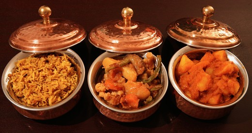 Stock Photo: 4286R-1694 Bowls of curry and rice lined up. From the left, coconut pilau rice, vegetable curry and Punjabi potato curry.