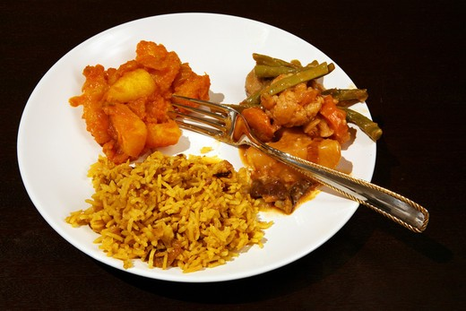 Stock Photo: 4286R-1696 An Indian vegetarian meal: coconut pilau rice with vegetable curry and Punjabi potato curry on a dark wood table.