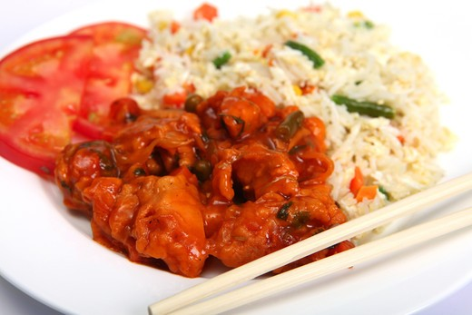 Stock Photo: 4286R-1994 Chicken sweet and sour with vegetable fried rice on a plate with chopsticks