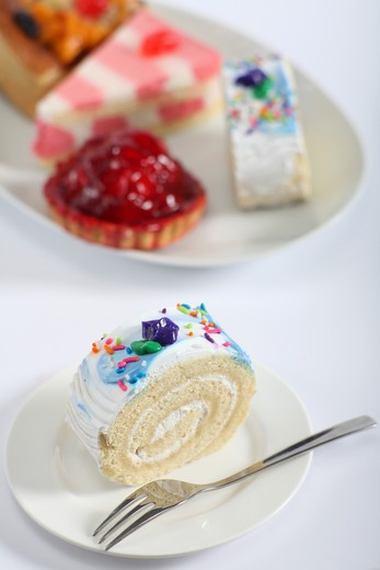 A colourful sponge roll with a fork and a plate of other cakes in the background : Stock Photo
