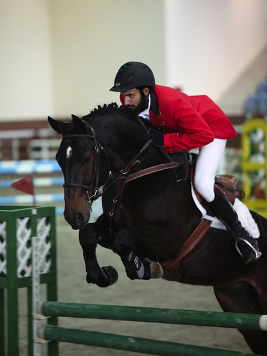 A regional showjumping competition at the Qatar Equestrian Federation's indoor arena in Doha : Stock Photo
