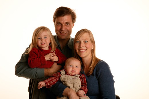 Stock Photo: 4286R-2285 Studio shot of a mother and a father holding their young daughter and baby.