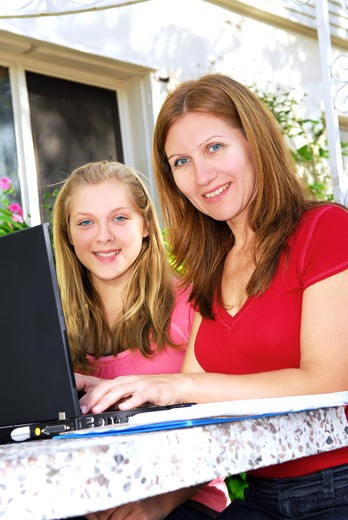 Mother and daughter working on a portable computer at home in the garden : Stock Photo
