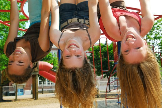 Stock Photo: 4286R-2775 Three young girls hanging upside down in a park and laughing